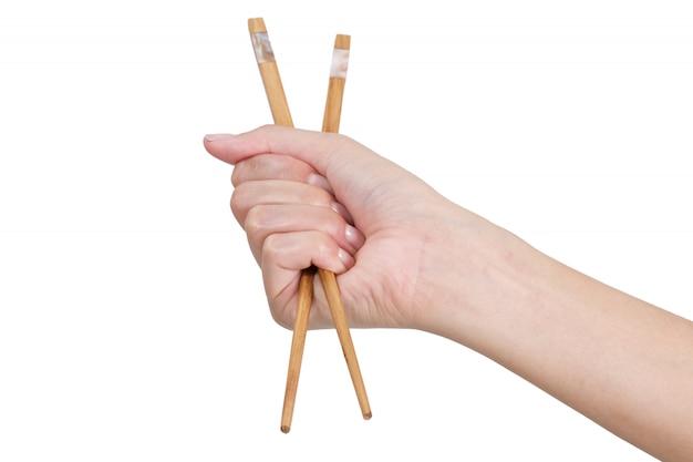 Main de femme tenant des baguettes isolés sur blanc