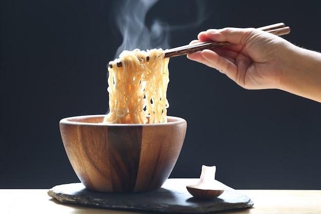Main de femme tenant des baguettes de nouilles instantanées dans une tasse avec de la fumée montante et de l'ail sur fond sombre, régime sodique insuffisance rénale à haut risque, concept d'alimentation saine