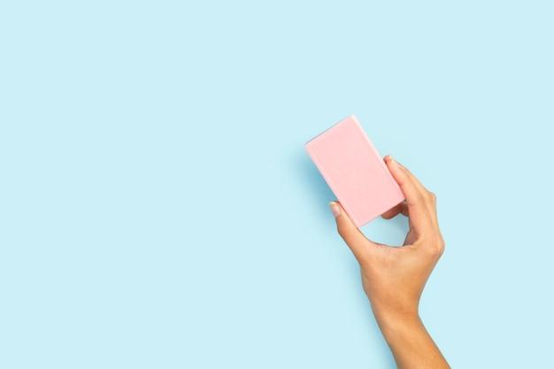 Main de femme tenant une barre de savon rose sur fond bleu clair