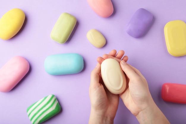 Main de femme tenant une barre de savon rose sur une surface violette