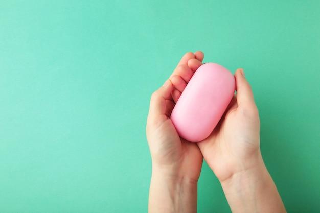 Main de femme tenant une barre de savon rose. vue de dessus