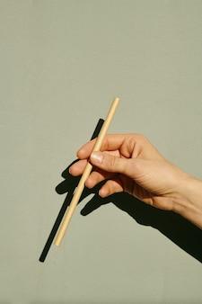Main de femme tenant un bâton devant la caméra sur un mur gris
