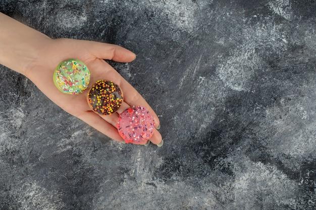 Main de femme tenant des beignets sucrés colorés avec des pépites.