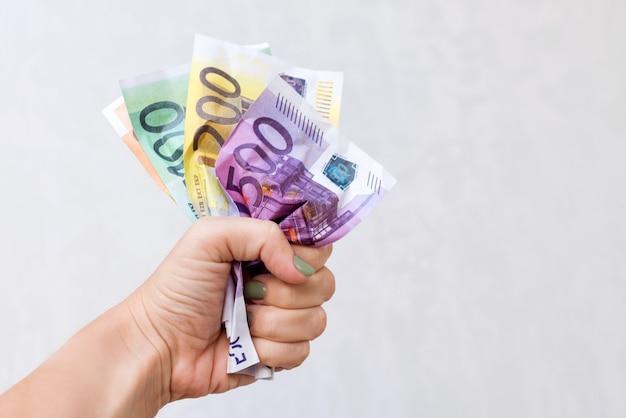 Main de femme tenant des billets en euros froissés.