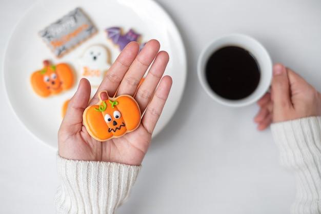 Main de femme tenant un biscuit d'halloween drôle pendant qu'il boit du café. joyeux halloween, astuce ou menace, bonjour octobre, automne automne, concept traditionnel, fête et vacances
