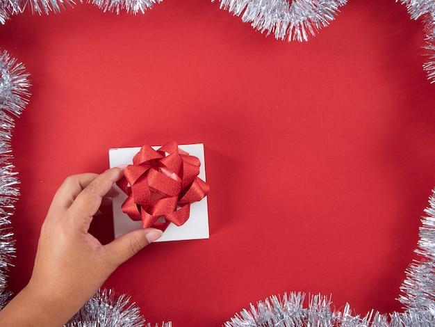 Main de femme tenant une boîte cadeau attachée avec un ruban rouge