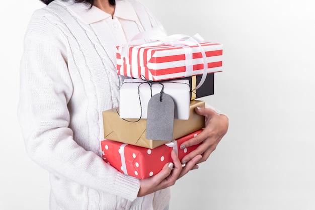 Main de femme tenant la boîte-cadeau et l'étiquette en papier isolé sur fond blanc pour le concept de noël et du nouvel an.