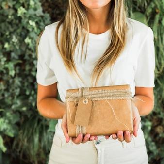 Main de femme tenant une boîte cadeau marron