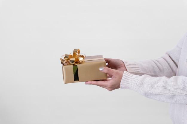 Main de femme tenant la boîte-cadeau or sur fond blanc.