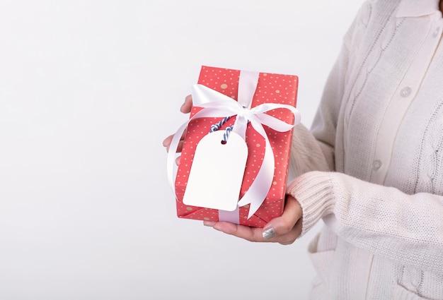 Main de femme tenant une boîte-cadeau rouge et une étiquette en papier isolé sur fond blanc pour le concept de noël et du nouvel an.