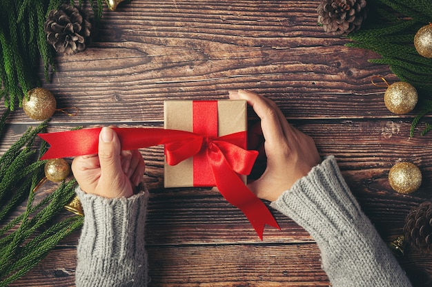 Main de femme tenant une boîte-cadeau avec ruban rouge sur plancher en bois