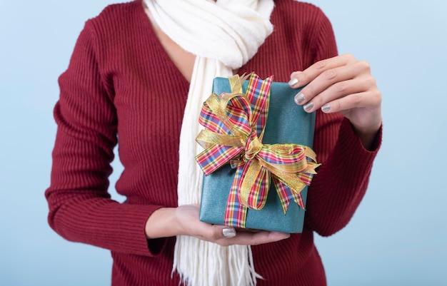 Main de femme tenant une boîte cadeau verte sur fond bleu pour le concept de noël et du nouvel an.