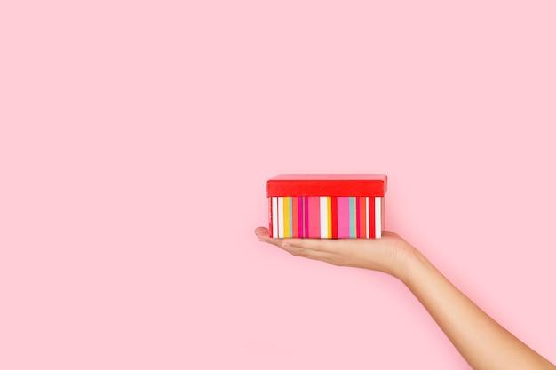 Main de femme tenant une boîte rayée sur fond rose avec espace copie