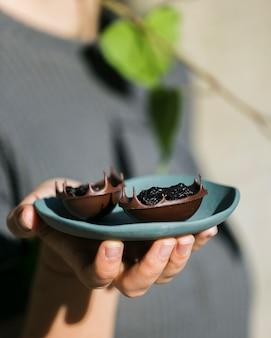 Main de femme tenant des bols à dessert savoureux dans une assiette en céramique