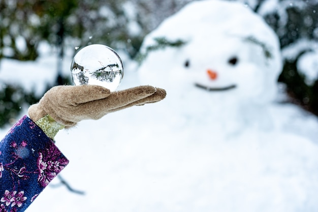 La main d'une femme tenant une boule de cristal à côté d'un bonhomme de neige.