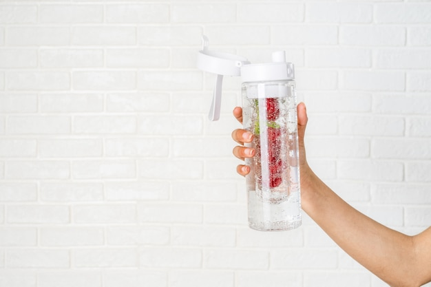 Main de femme tenant une bouteille avec de l'eau de désintoxication infusé