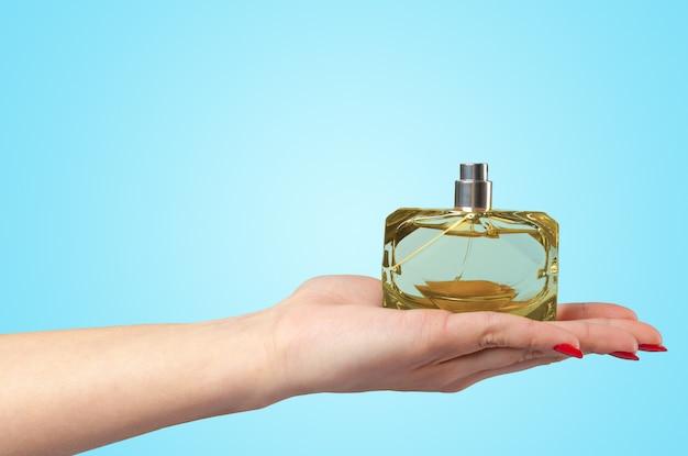 Main de femme tenant une bouteille de parfum isolée sur fond de couleur