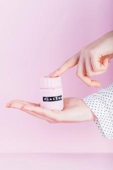 Main de femme tenant une bouteille de placebo sur fond rose