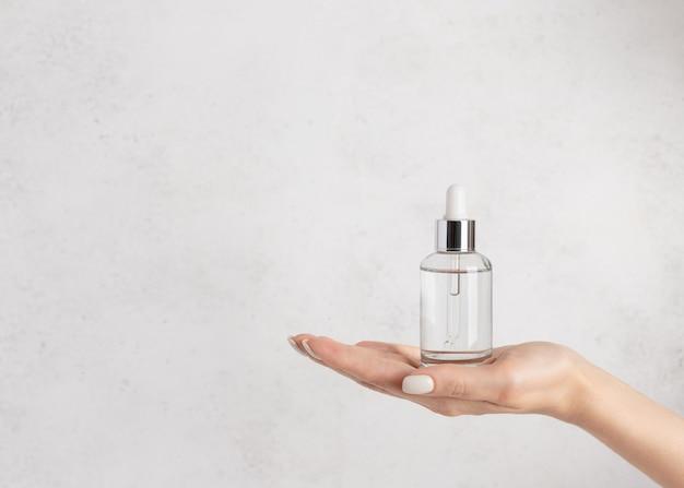 Main de femme tenant une bouteille en verre avec du sérum hydratant