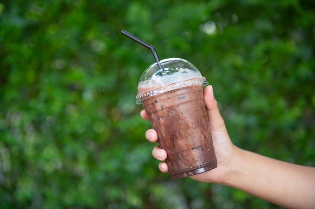 Main de femme tenant le café glacé en verre