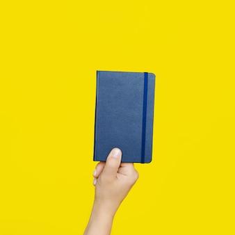 Main de femme tenant un cahier bleu fermé sur un mur jaune vif.