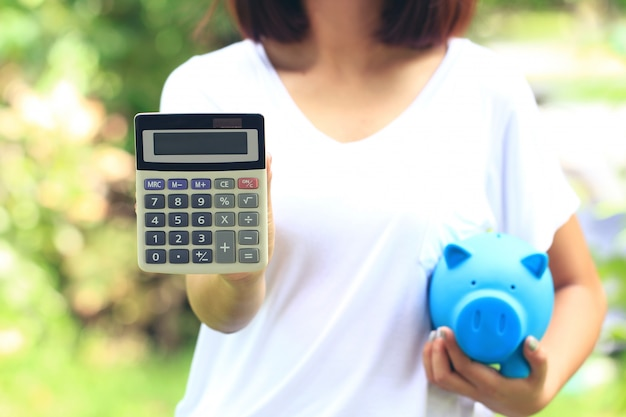 Main de femme tenant la calculatrice et le cochon bleu sur fond vert naturel, investissement et concept d'entreprise
