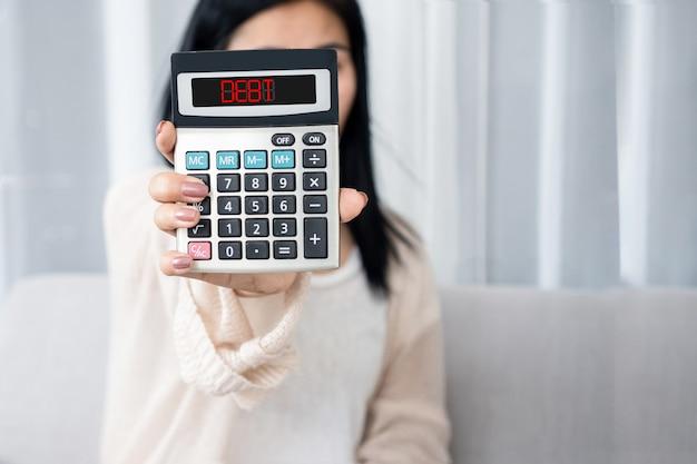 Main de femme tenant la calculatrice montrant le concept de problème financier de dette de mot