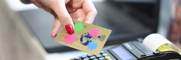 Main de femme tenant une carte bancaire avec un coronavirus près de voies de transmission de gros plan de caisse enregistreuse