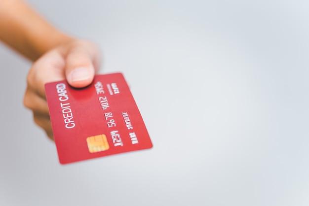Main de femme tenant une carte de crédit sur un fond blanc. paiement en ligne pour les achats en ligne