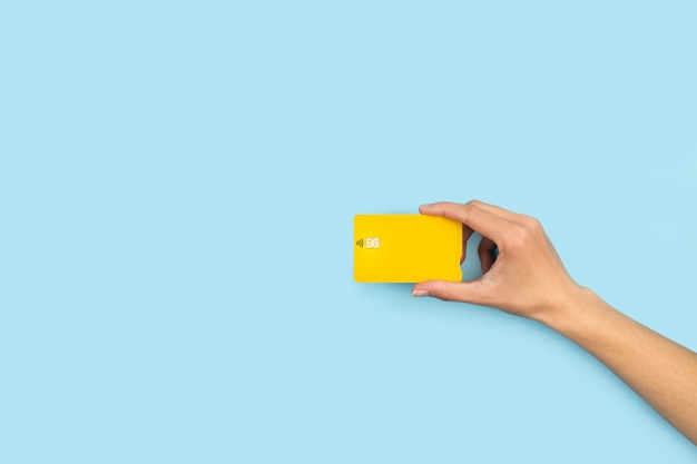 Main de femme tenant une carte de crédit jaune sur fond bleu clair