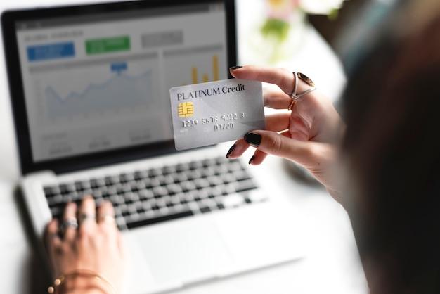 Main de femme tenant une carte de crédit platine avec fond d'ordinateur portable