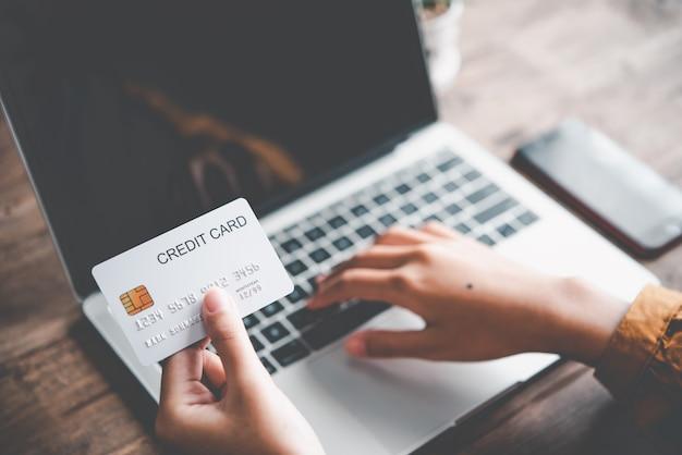 Main de femme tenant une carte de crédit et travaillant sur un ordinateur portable. paiement en ligne pour les achats en ligne