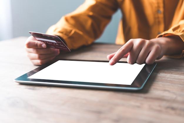La main d'une femme tenant une carte de crédit et travaille presque sur le bit. paiement en ligne pour les achats en ligne
