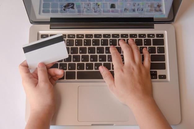 Main de femme tenant une carte de crédit et utilisant un ordinateur portable en ligne. paiement en ligne, achats en ligne