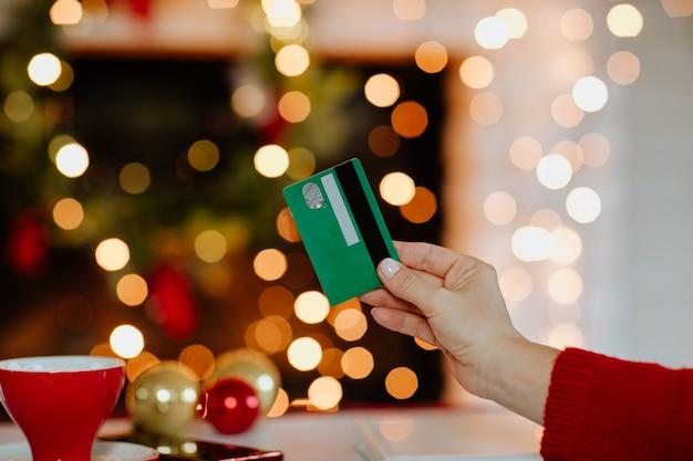Main de femme tenant une carte de crédit verte contre noël
