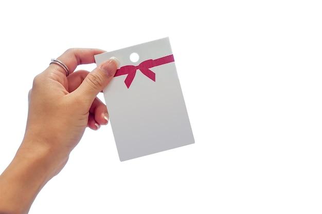 Main de femme tenant la carte en papier blanc avec un motif d'arc rouge dessus. c'est une image isolée sur un écran blanc.
