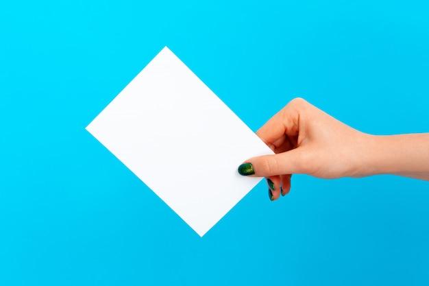 Main de femme tenant une carte vierge sur bleu