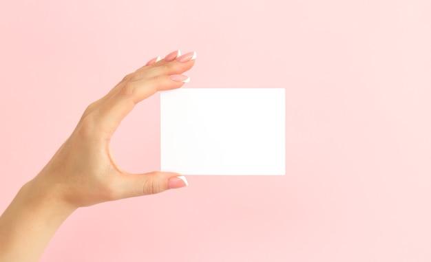 Main de femme tenant une carte de visite blanche vierge, une remise ou un dépliant sur fond rose