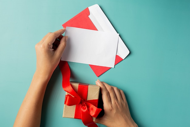 Main de femme tenant une carte de voeux et une boîte-cadeau