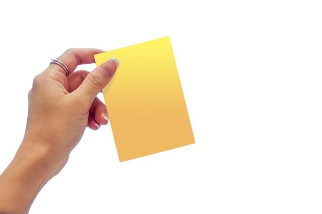 Main de femme tenant le carton jaune sur fond clair blanc.