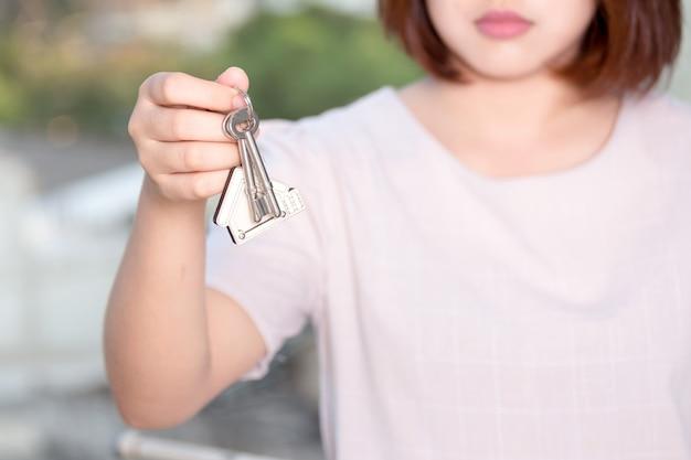 Main de femme tenant la clé de la maison. concept pour les affaires immobilières.
