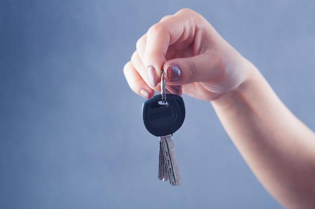 Main de femme tenant les clés de la porte