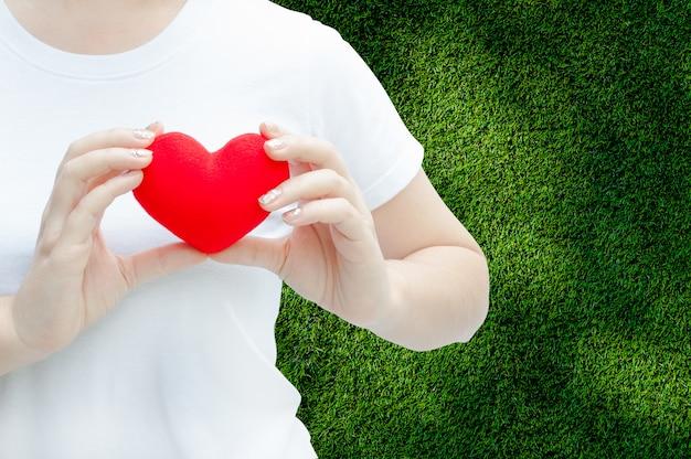 Main de femme tenant un coeur rouge en peluche à gauche de sa poitrine, concept de la saint-valentin, coeur d'amour, protéger et soins de santé