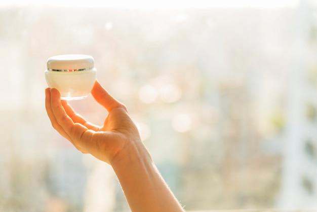 Main de femme tenant un contenant de crème cosmétique