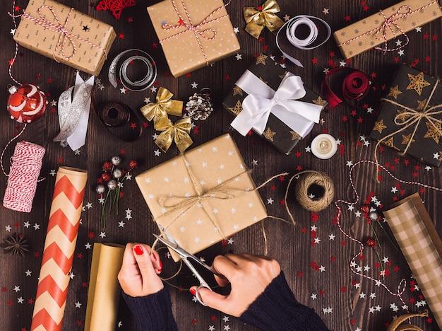 Main de femme tenant une corde de ficelle avec des ciseaux pour couper et emballer une boîte de cadeau de noël
