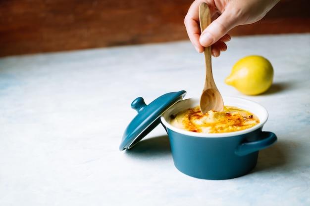Une main de femme tenant une cuillère en bois pour manger un délicieux houmous à l'huile d'olive et au paprika