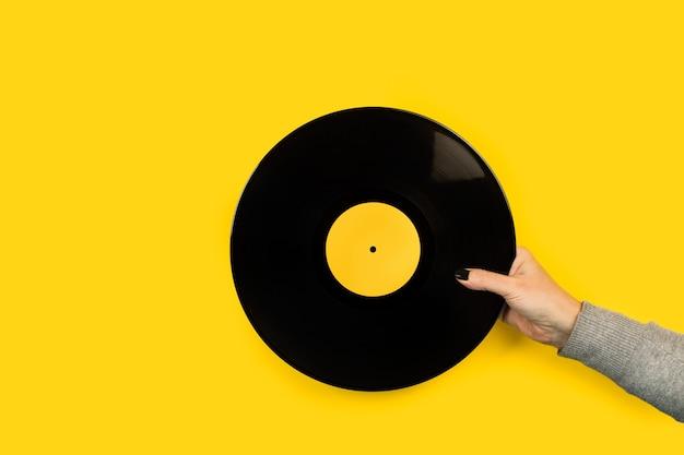 Main de femme tenant un disque vinyle sur fond jaune