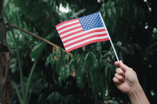 Main de femme tenant le drapeau des etats-unis sur la forêt verte. 4 juillet fête de l'indépendance américaine