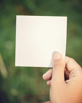 Main de femme tenant du papier vierge sur la nature