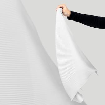 Main de femme tenant une écharpe plissée blanche à la mode